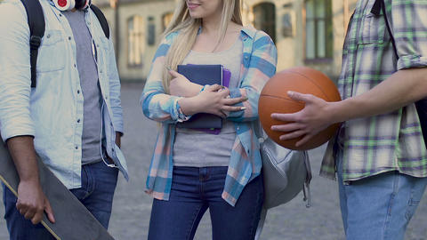 Popular college girl standing between two guys, choosing date, affection Live Action