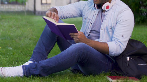 Multiethnic man sitting on grass reading book, recreational activity, bookworm Live Action