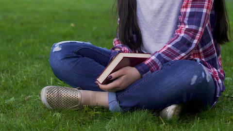 Young woman sitting on grass, holding closed book, recreational activity, relax Live Action