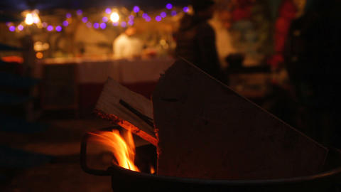 Logs peacefully crackling in fire on background of festive Christmas market Footage