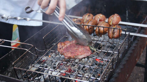 Chef cooking meat and vegetables on barbecue in fresh air, street food festival Live Action