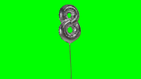 Number 8 eight years birthday anniversary silver balloon floating on green Live Action
