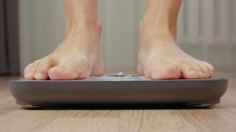 Male foot stepping on weight scale for weighting close up. Health and wellness Live Action