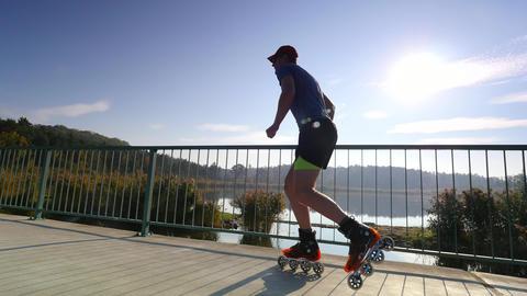 Sportsman on roller skates at summer. Inline skating on the lake road. Live Action