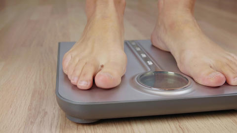 Close up male or woman foot stepping on weight scale for weighting body Footage