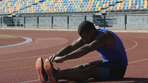 Hispanic athlete completing set of daily exercises sitting on running track Footage