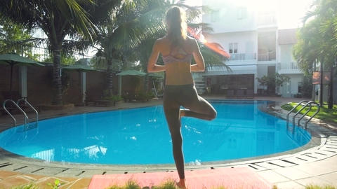 girl balances in yoga position by pool in morning backside Footage