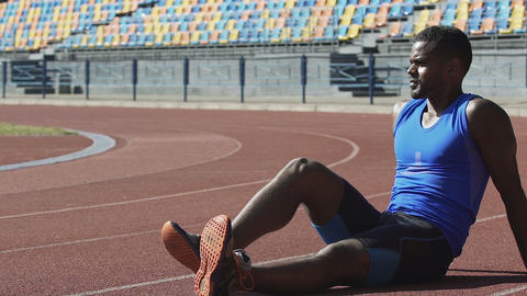 Handsome man in sports wear sitting on running track taking breath and resting Footage