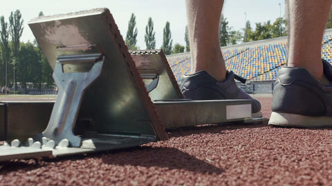 Runner putting his feet on footplates of starting blocks and runs after command Live Action