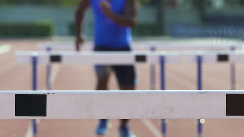 Man running hurdle race, feeling strength and excellence in professional sport Live Action