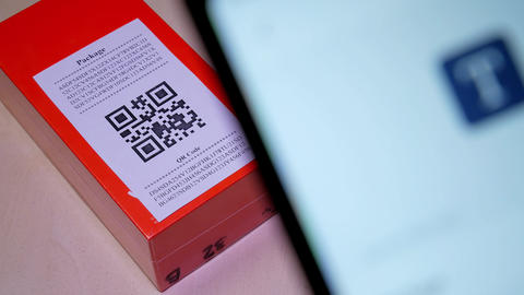 Smartphone scanning QR code in paper label on the orange package or parcel box GIF