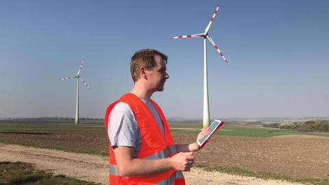 Technician uses tablet looking at wind turbine Footage