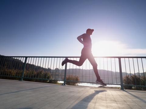 Man is running quickly on the shore bridge. Silhouette of active man Fotografía