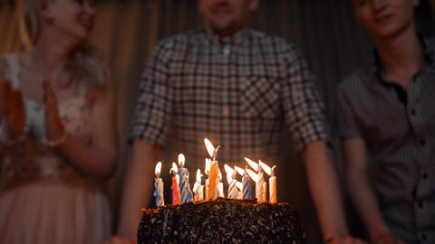 Young man blows out candles on a festive cake with friends near Footage