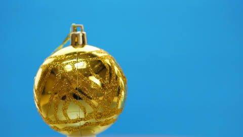 Decorated yellow Christmas balls spinning on blue background GIF