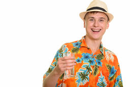 Young happy Caucasian man smiling and holding glass of water フォト