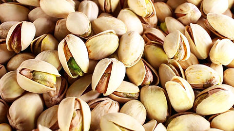 Pistachio texture. Nuts. Green fresh pistachios as texture. Roasted salted Live Action