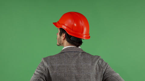 Rear view portrait of a contractor wearing hardhat looking at the green screen Archivo