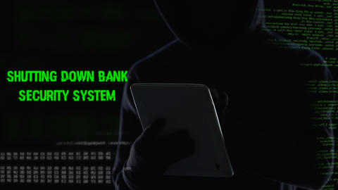 Criminal shutting down bank security system on tablet, illegal funds transfer Live Action