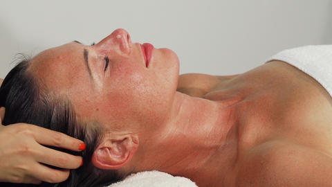 Happy beautiful mature woman smiling while getting head massage Live Action