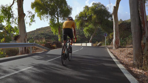 A man on a sports road bike rides on the road located high in the mountains. in Footage