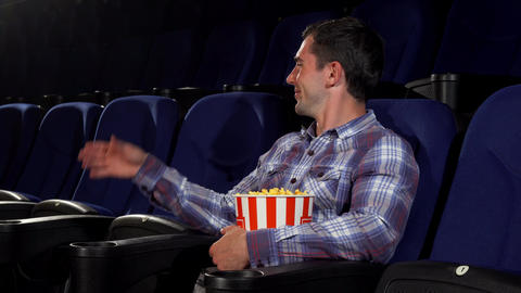 Happy handsome man smiling joyfully sitting at the cinema Footage