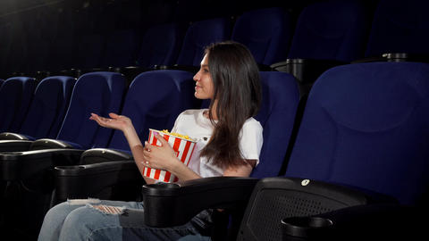 Attractive young woman enjoying movies at the cinema Footage