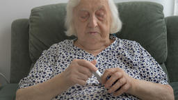 An elderly woman paints her lips with lipstick Footage