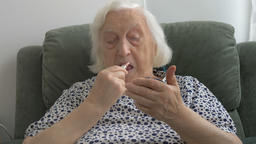 An elderly woman paints her lips with lipstick Stock Video Footage