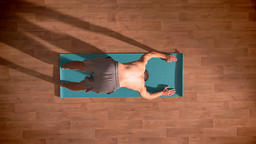 Top shot, fit caucasian male doing yoga stretching on blue mat , keeping his ビデオ