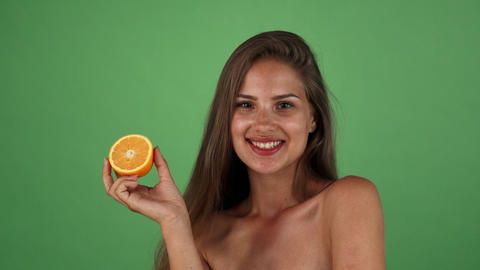 Studio shot of a gorgeous happy woman smiling holding half of an orange Live Action