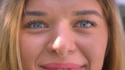 Close-up big blue eyes of caucasian woman who is looking straight and smiling Footage