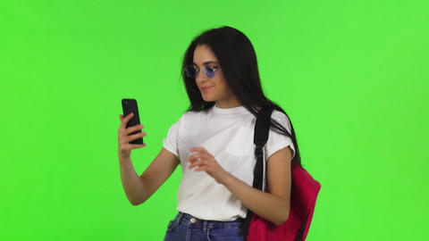 Charming female student with a backpack taking selfies with her smart phone ビデオ
