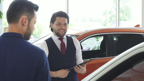 Handsome male car dealer talking to his male customer Live Action