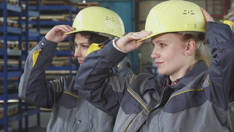 Female engineers wearing protective hardhats smiling to the camera Footage