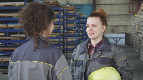 Young beautiful hardware storage female worker talking to her colleague Live Action