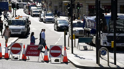 Many people crossing street in London, UK, road closed sign Footage