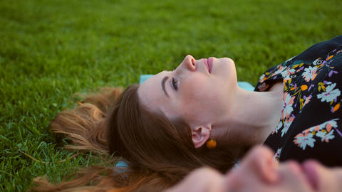 Happy Smiling Couple Relaxing on Green Grass. Female in focus Footage