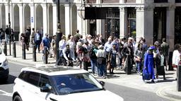 Many people walking on sidewalk crowd tourists in London, UK Footage
