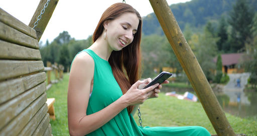 4k - girl sitting on the swing bench and use her phone in the mountains Archivo