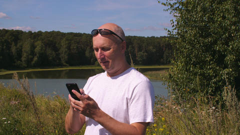 Adult man holding mobile phone and typing message in summer park ビデオ