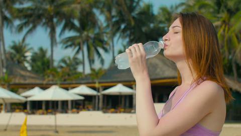 Girl drinks cold water at sunny beach Footage