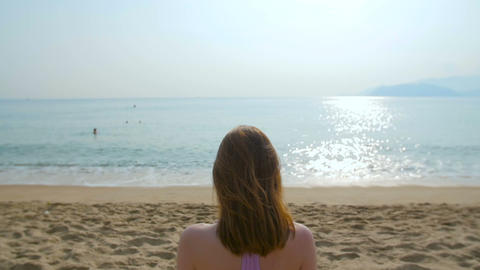 Young beautiful woman sitting on the beach, meditation, slow motion Footage