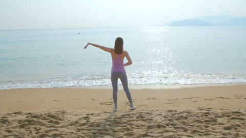 Young woman doing exercises on the beach at sunrise Footage