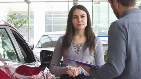 Young woman talking to the salesman at the car dealership Live Action