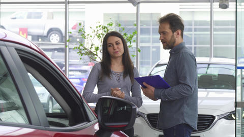 Mature salesman talking to his female customer offering her a car Live Action