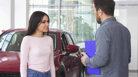 Gorgeous happy woman shaking hands with car dealer after receiving car keys Live Action