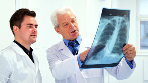 Two male doctors look at x-ray Live Action