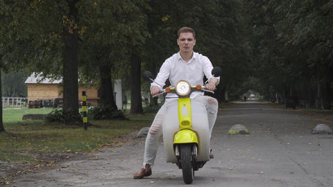 Smiling guy riding a scooter Footage