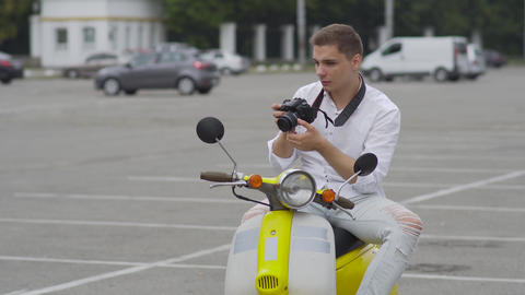 Handsome guy on a retro motorbike makes a photo Footage
